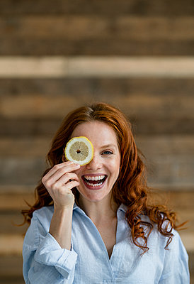 Portrait of laughing redheaded woman covering eye with lemon slice - p300m2140736 by Kniel Synnatzschke