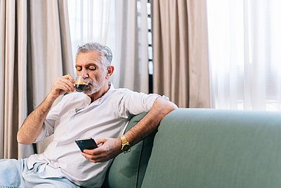 Mature man having coffee using smart phone while sitting on sofa in hotel room - p300m2250499 by Daniel González