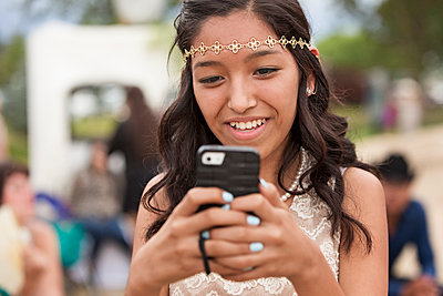 Hispanic girl using cell phone outdoors - p555m1410166 by Hill Street Studios
