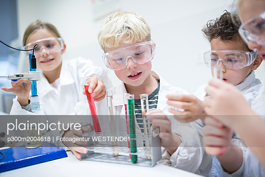 Pupils in science class experimenting with liquids in test tubes - p300m2004618 von Fotoagentur WESTEND61