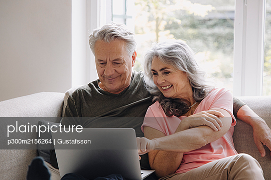 Happy senior couple with laptop relaxing on couch at home - p300m2156264 by Gustafsson