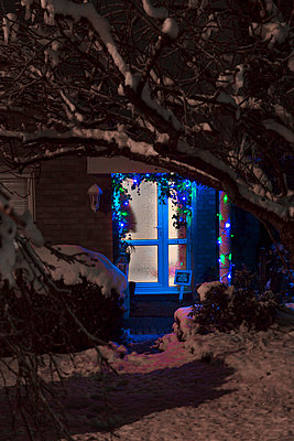 Looking at the front foor of a house trhoughtrees covered in snow with fairly ligths and christmas decorations glowing in the doorway, porch and windows. - p1057m1510397 by Stephen Shepherd