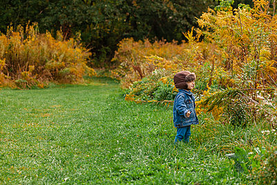 A small toddler stands bundled up in a golden field in autumn - p1166m2131332 by Cavan Images