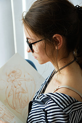 millennial girl draws fabulous images on paper while sitting at home - p1166m2171828 by Cavan Images