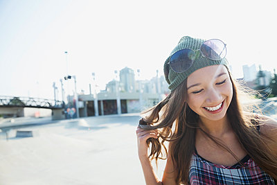 Smiling teenage girl with hand in hair - p1192m1014252f by Hero Images