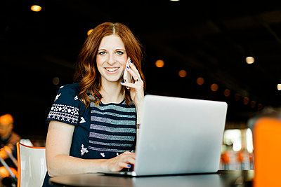 Smiling mid adult woman using smart phone and laptop - p1427m2128247 by Jessica Peterson