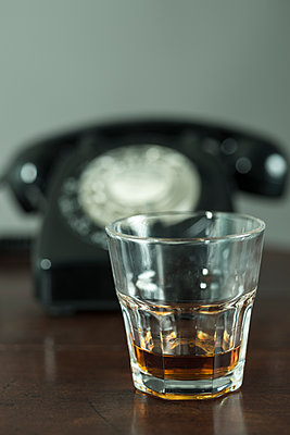 A glass of liquor before blurred 1950s 1960s black telephone. - p1433m1589808 by Wolf Kettler