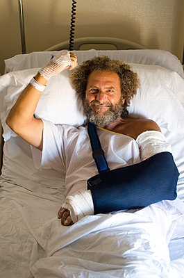 Middle-aged man in hospital with one broken arm and raising the other arm with positive attitude - p1656m2248598 by Javier Martinez Bravo