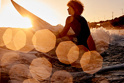 Surfer in the sea at sunset - p300m1205373 by Fotoagentur
