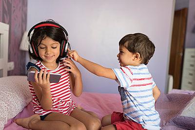 Portrait of smiling girl listening music with headphones while her little brother disturbing her - p300m2029280 von Jaen Stock