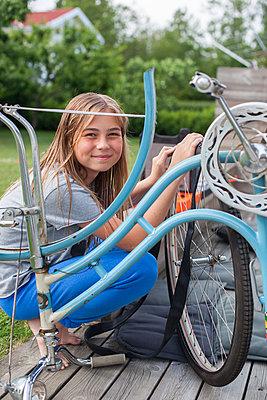 Girl repairing bicycle - p312m1470923 by Christina Strehlow