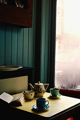 Tabletop with tea cups saucers and a teapot in a cafe setting - p349m695107 by Emma Lee