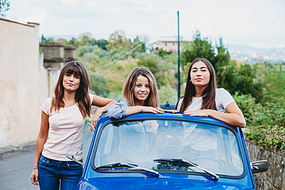 Woman standing beside friends posing in car sunroof, Florence, Toscana, Italy - p429m2097535 by Lorenzo Antonucci