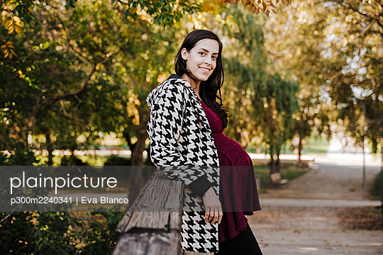 Smiling pregnant woman leaning on wooden structure in park - p300m2240341 by Eva Blanco