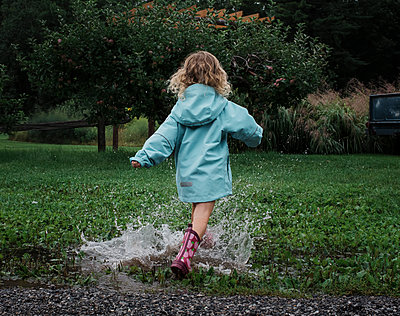 Rear view of playful girl splashing water in puddle at apple orchard - p1166m2024811 by Cavan Images