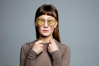 Junge Frau blickt durch Teesiebe - p1212m1092874 von harry + lidy