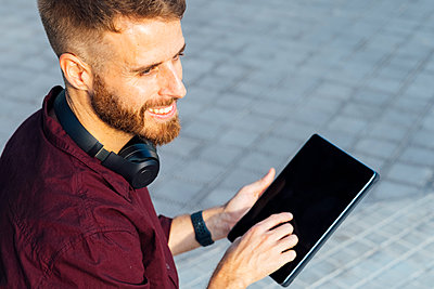Smiling businessman looking away while using digital tablet standing on footpath - p300m2250830 by Boy photography