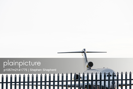 An old jet aircraft standing on the outskirts of an airfield behind a large metal security fence. - p1057m2141775 by Stephen Shepherd