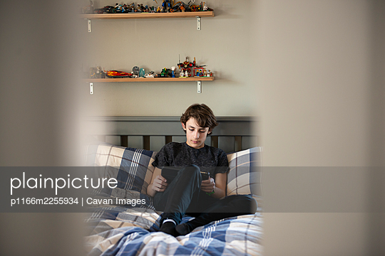 Looking through door at tween boy sitting on his bed with a tablet. - p1166m2255934 by Cavan Images