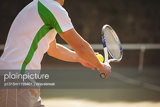 Man with tennis racket ready to serve