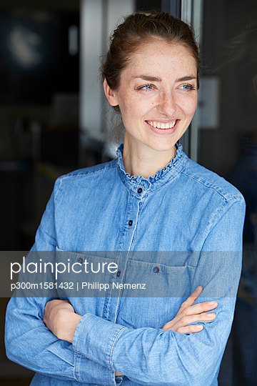Portrait of smiling woman wearing denim shirt leaning against open window - p300m1581432 von Philipp Nemenz
