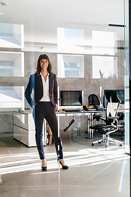 Successful businesswoman standing in office with hands in pockets - p300m1487438 by Kniel Synnatzschke