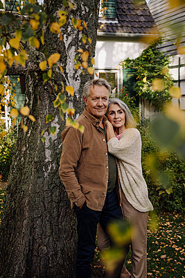 Senior couple in garden of their home in autumn - p300m2156255 by Gustafsson