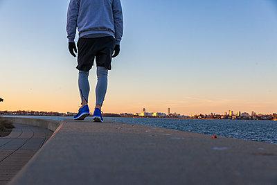 Man in sportswear standing on coastline - p343m1443245 by Lucie Wicker