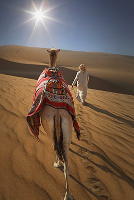 Rear view of bedouin leading camel in desert, Dubai, United Arab Emirates - p429m1021623f by Lost Horizon Images