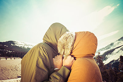 Caucasian couple hugging in parka hoods near mountain - p555m1413181 by Dave and Les Jacobs