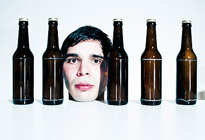 Portrait of a man in between bottles of beer - p7170010 by Oliver Rüther