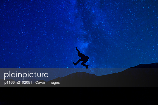 Silhouette Jumping Under Milky Way Night Stars Extreme Creative Concept - p1166m2192051 by Cavan Images