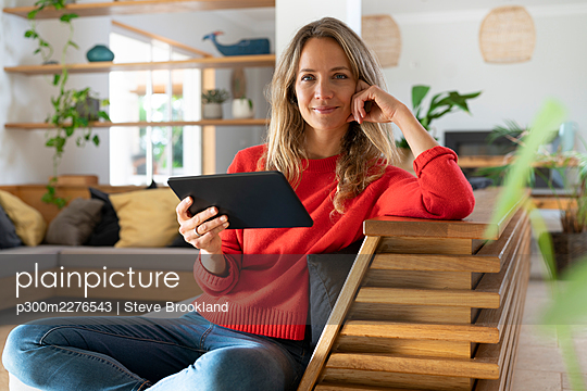 Happy woman holding tablet while sitting on couch at home - p300m2276543 by Steve Brookland