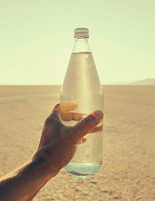 The landscape of the Black Rock Desert in Nevada. An essential element for survival. A man's hand holding a bottle of water. Filtered mineral water.  - p1100m875892f by Paul Edmondson