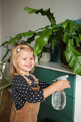 Smiling child with water sprayer in hands watering plants at home - p1166m2189908 by Cavan Images