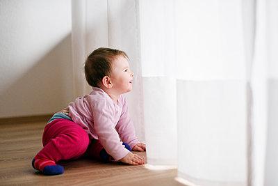 Baby blickt durch Vorhang - p1196m1201695 von Biederbick & Rumpf