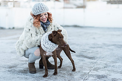 Happy young woman with her dog in winter - p300m1581017 von Jaen Stock