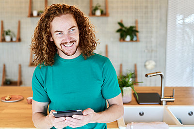 Smiling man looking away while using digital tablet in kitchen of studio apartment - p300m2225518 by Jo Kirchherr