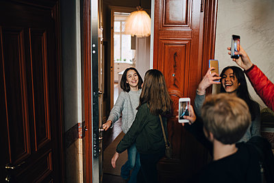 Happy friends photographing girls while standing at doorway - p426m1555924 by Maskot