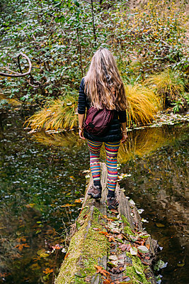 A woman walks across a log over a tranquil stream in autumn; California, United States of America - p442m2019798 by Dean Blotto Gray