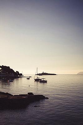 Segelboote in kleiner Buch bei Sonnenuntergang - p946m951529 von Maren Becker