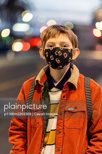 Portrait of teenager wearing mask during COVID 19 pandemic in city - p1166m2269369 by Cavan Images