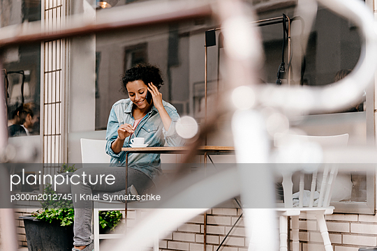 Young woman drinking coffee in front of cafe, talking on the phone - p300m2012745 von Kniel Synnatzschke