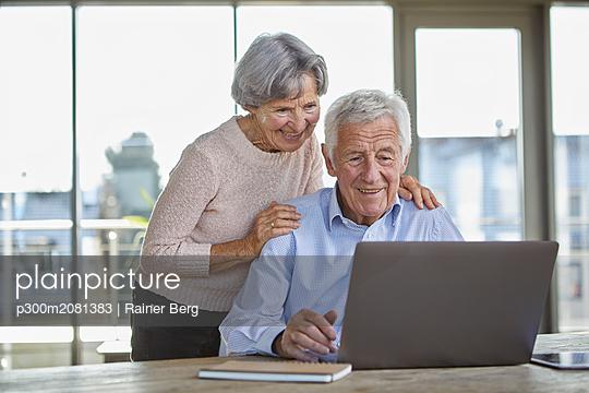 Portrait of smiling senior couple using laptop - p300m2081383 by Rainer Berg