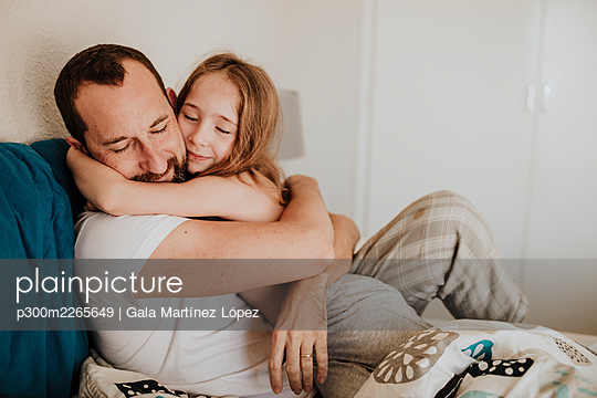 Daughter leaning on father while hugging on bed at home - p300m2265649 by Gala Martínez López