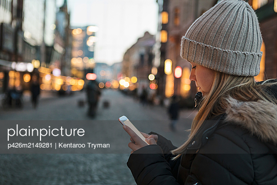 Teenage girl wearing knit hat text messaging on smart phone in city during sunset - p426m2149281 by Kentaroo Tryman