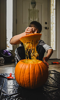 Boy removing seeds from fresh pumpkin at home - p1166m2066504 by Cavan Images