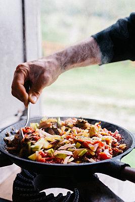 Mann bereitet Gemüsepfanne draußen über Gasflamme zu  - p1497m2149554 von Sascha Jacoby