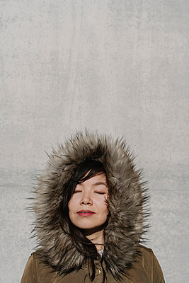 Portrait of woman in winter coat in the background of a wall - p300m2154571 by Hernandez and Sorokina