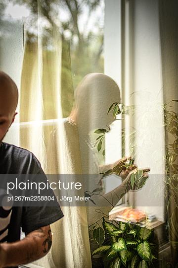 Reflection of bald man in window pane - p1267m2258804 by Jörg Meier
